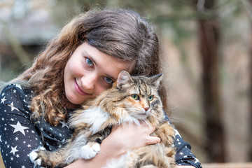 Happy young woman in black dress holding maine coon cat outside, outdoors during summer in park