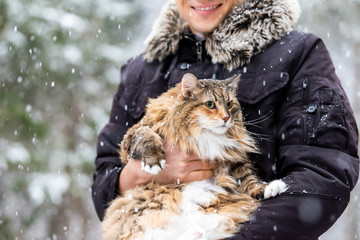 Closeup of young happy man holding maine coon cat outside, outdoors in park in snow, snowing