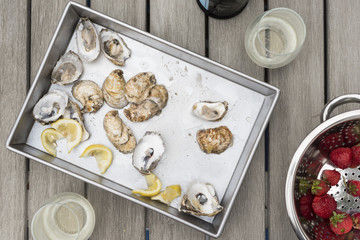 Tray of raw oysters on a wooden table