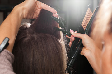 professional hairdresser clipping hair of a young model with a hairpin before making a gauffer hairdo in a beauty salon