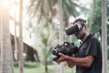 Man in virtual reality headset playing video game in tropical tree