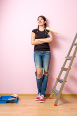 Image of young woman with paint roller standing near staircase