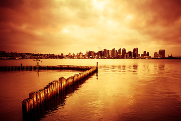 Wall Mural - Beautiful sunset over San Diego skyline with bay and and line of wooden posts