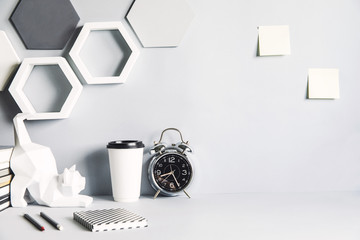Modern and design space with cat figures, clock, memo sticks, office accessories and cup of coffee. Gray interior with hanging hexagone shapes. Design gray room.