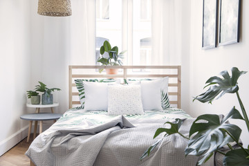 Modern scandinavian sunny bedroom with plants , floral pattern bedding and pilows. Space with white...