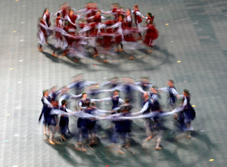 People wear traditional dress as they dance during the folk dance show at the Song and Dance Celebration in Riga