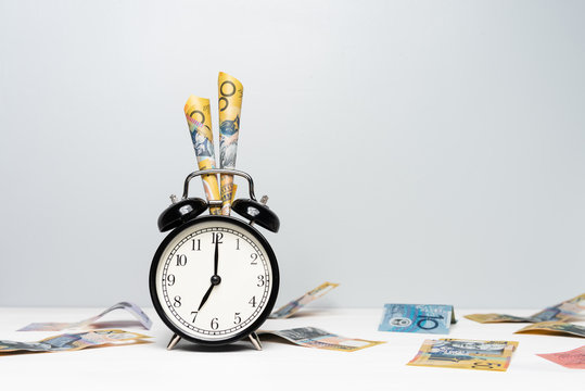 Clock and Australian money on light color background. Time is Money. Tax season concept.