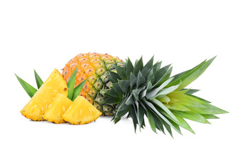 whole and slices ripe pineapple with leaves isolated on white background