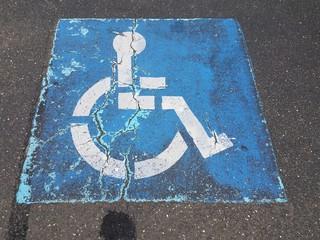 cracked blue handicap or wheelchair sign on asphalt