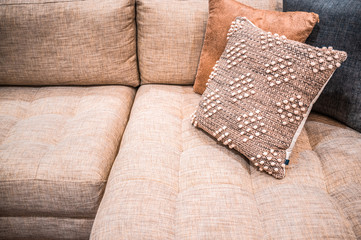 Beige pillows and textile couch closeup - interior design