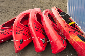 Empty red plastic recreational kayaks for rent or hire, stored on sandy beach after hours on a rainy day. Crescent Beach, Surrey, British Columbia, Canada.