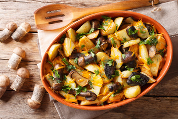 Fried potatoes with boletus mushrooms, cheddar cheese and herbs close-up in a platter. Horizontal top view