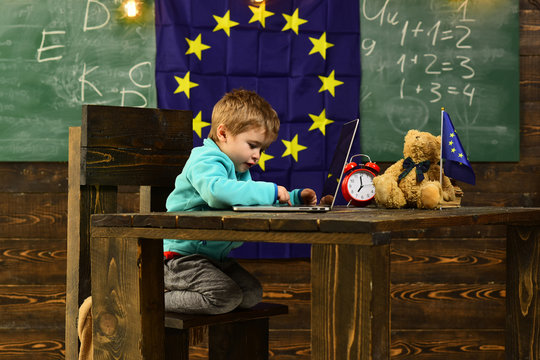 New technology. Little child use laptop computer in classroom with eu flag, new technology. New technology in elementary school. New technology for back to school. Tomorrow starts here