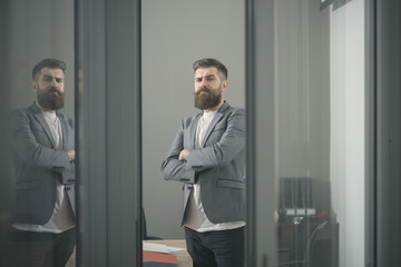 Confidence and success concept. Bearded man look out room door. Businessman in modern office with glass walls. Confident man in casual suit at working place. Business and office lifestyle