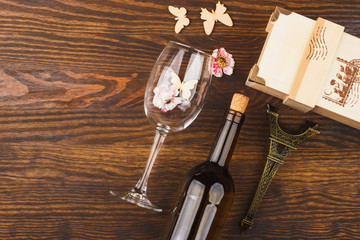 Wineglass and bottle with decorative flowers and butterflies