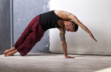 Young strong male practices yoga and gymnastics, flexibility and stretching