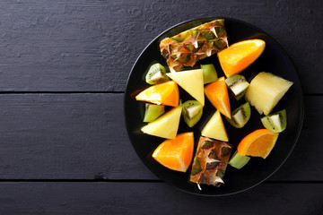 Fruit salad on a black plate on wooden boards, pineapples, oranges and kiwi on a dark background, salad of tropical fruits for breakfast, vegetarian food, copy space