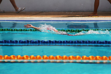 Young swimmer practice backstroke or back crawl in swimming pool