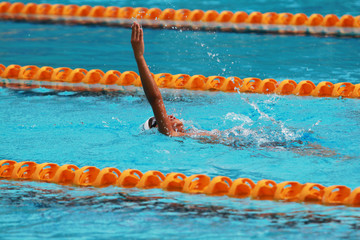 Swimmer swims backstroke or back crawl in a swimming pool for competition or race