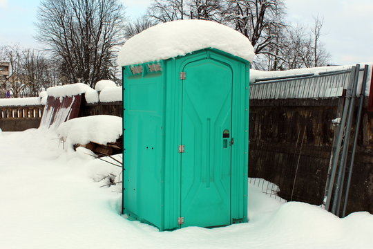 Portable ecological toilet covered and surrounded with freshly fallen snow, wire fence and building material on construction site during winter