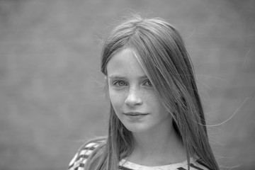 Beautiful blond young girl with freckles outdoors on wall background, closeup portrait, black and white