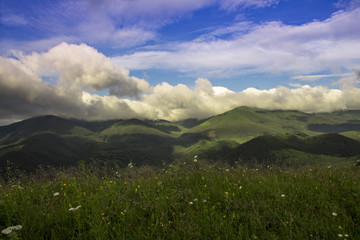 Photo of mountain landscape in the summer under beautiful cloudy sky. Ukraine, Carpathians, Dzembronia village.