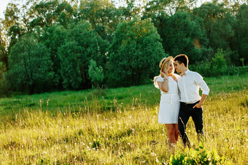 Awsome happy couple have fun in a field sunset background. Handsome Caucasian guy wearing white shirt gentle hugs a smiling girl with blond hair in white dress. Lifestyle and travel concept.