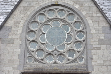 Round stained glass windows on stone early English style church in Ireland.