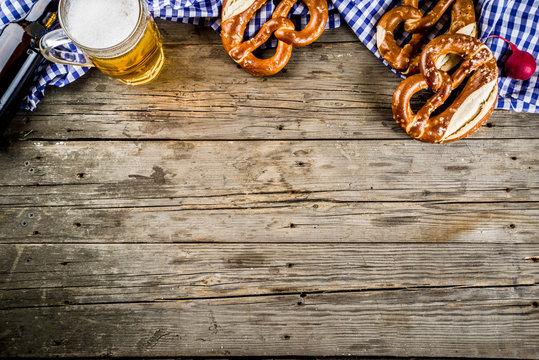 Oktoberfest food menu, bavarian pretzels with beer bottle mug on old rustic wooden background, copy space above