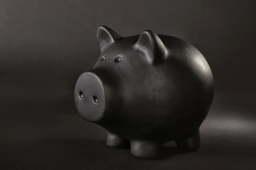 Black piggy bank on table against dark background