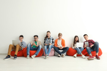 Group of teenagers with modern devices sitting near white wall