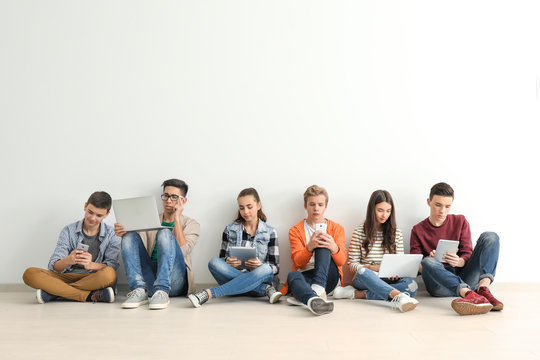 Group of teenagers with modern devices sitting on floor near wall