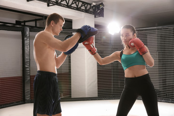 Young female boxer training in gym with personal coach