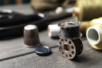 Bobbins with threads on table. Tailoring accessories
