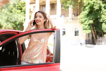 Young woman talking on phone near car outdoors