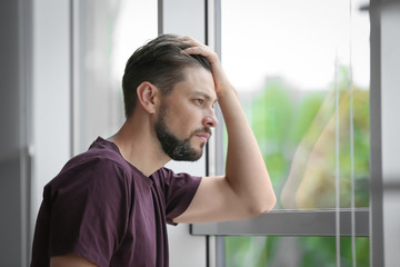Lonely depressed man near window at home Wall mural