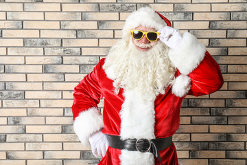 Authentic Santa Claus wearing sunglasses on brick wall background