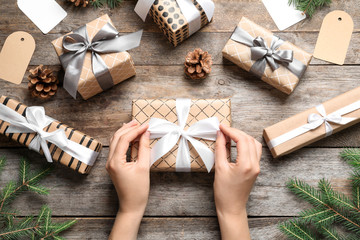 Fotobehang - Woman wrapping Christmas gift at wooden table, top view