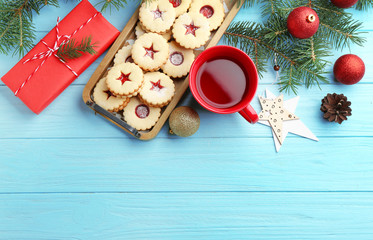 Christmas items and Linzer cookies with sweet jam on wooden background, top view