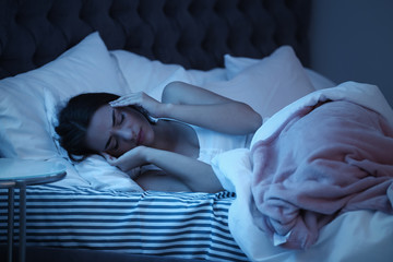 Young woman suffering from headache while lying in bed at night. Sleeping problems