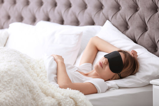 Young beautiful woman with mask sleeping in bed at home. Early morning