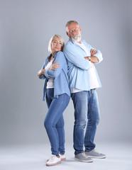 Upset mature couple on grey background. Relationship problems