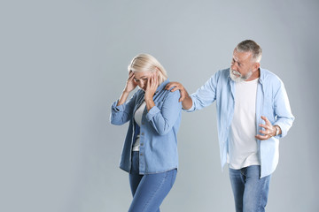 Mature couple having argument on grey background. Relationship problems