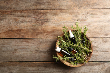 Bowl with bottles of rosemary oil and fresh twigs on wooden background, top view