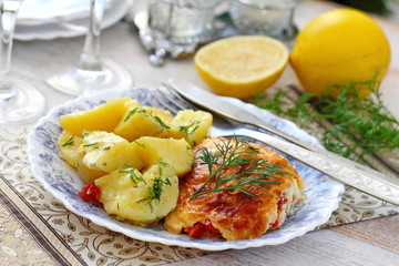 Fish fillet baked with tomato, greens and cheese served with boiled potatoes