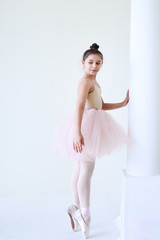 Beautiful little ballerina stands on the poine shoes before a column