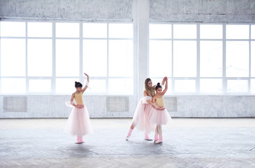 Teacher trains ballet moves with little girls in pink clothes in the room