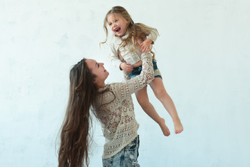 Beautiful mom and daughter dressed in casual style pose in the room
