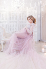 Beautiful pregnant woman in rich pink dress holds hands on her belly posing in luxury white room