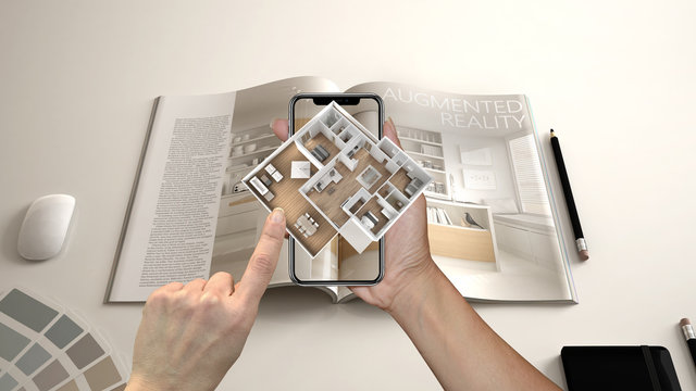 Augmented reality concept. Hand holding smartphone with AR application used to simulate 3d pop-up interactive house maps to life